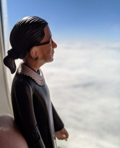 A figurine of Ruth Bader Ginsburg looks out an airplane window