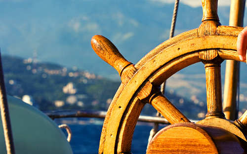 A hand on a steering wheel of a boat