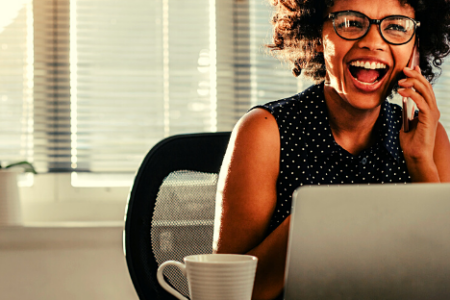 a woman sits at her desk and is happy